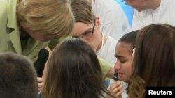 Канцлер Германии Ангела Меркель (слева) и палестинская школьница Рим Сахлвиль во время встречи в Ростоке, июль 2015 года.