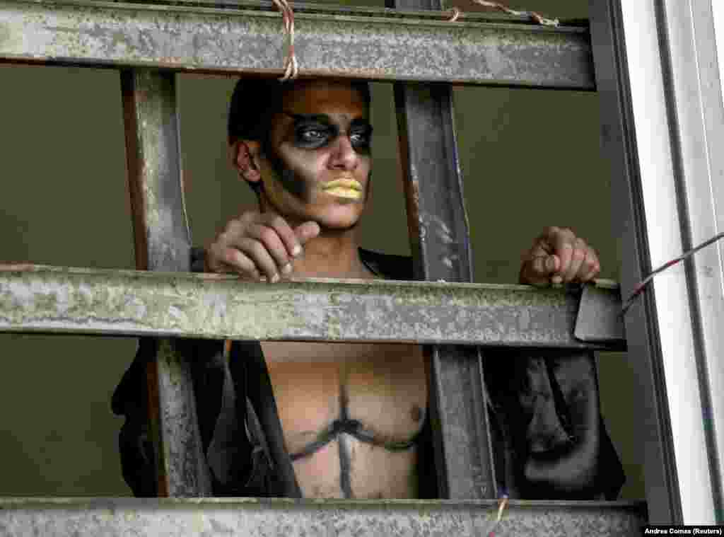 "An Iraqi actor in make-up looks out a window before a performance in Baghdad of ""Obey The Devil,"" a modern intepretation of Shakespeare's ""Othello."""