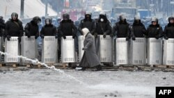 A woman walks in front of riot police on Hrushevskyy Street in central Kyiv.