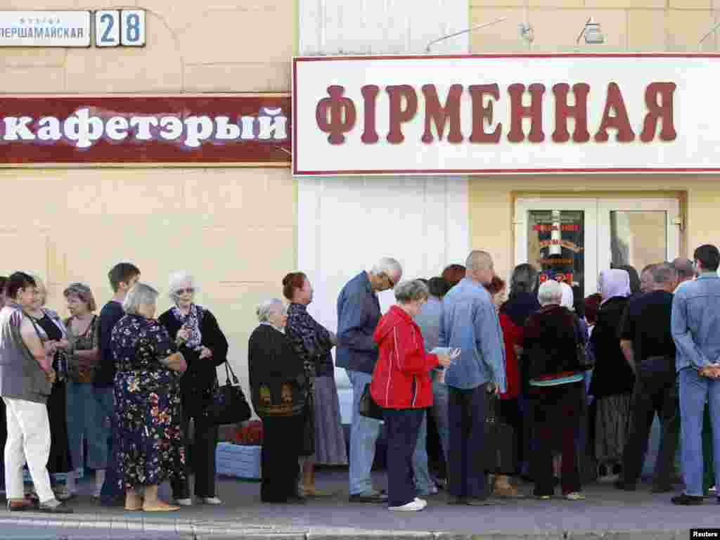 People wait in a line to buy meat in front of the closed door of a shop before it opens in Minsk on August 26.
