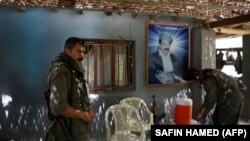 Members of the Kurdistan Workers' Party (PKK) rest in front of a portrait of jailed Kurdish rebel chief Abdullah Ocalan at a camp on July 29, 2015 deep in the Qandil mountain, the PKK headquarters in northern Iraq.