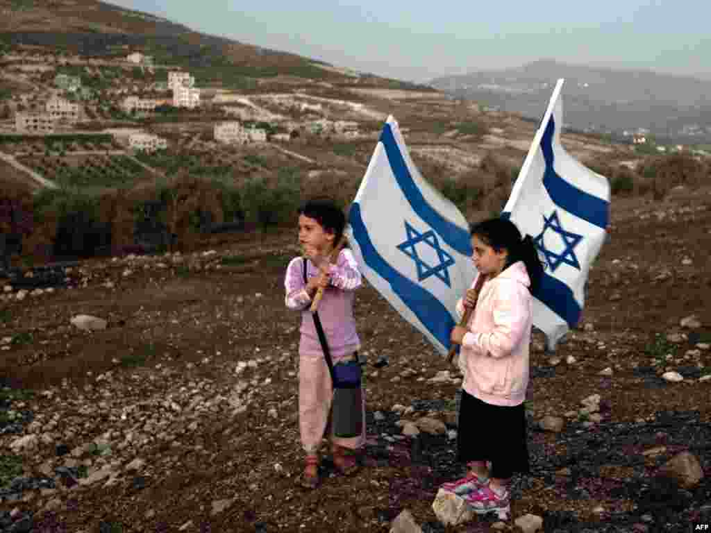 Two girls from the nearby Jewish settlement of Yits Har hold Israeli flags during a protest against the construction of a mosque in the Palestinian village of Burin in the Israeli-occupied West Bank, several kilometers from the northern city of Nablus, on October 4. The settlers claim they are not being allowed to build a synagogue while the local residents are allowed to construct a mosque. Photo by Jack Guez for AFP