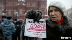 "A participant holds up a flyer saying ""We need Dozhd"" during a protest against the threat of closure of Dozhd TV in Moscow in February."