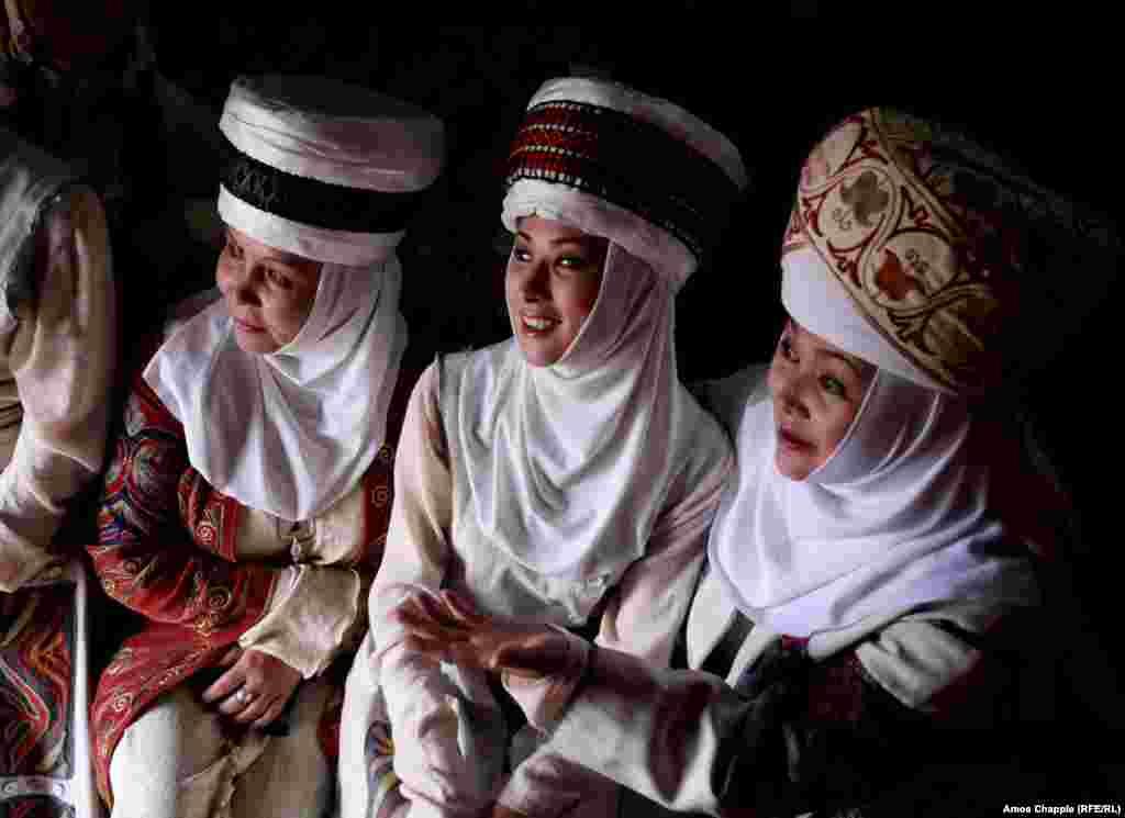 Three women from the Bishkek Drama Theatre wait out a rainstorm inside a yurt, after their performance was postponed.