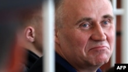 Mikalay Statkevich sits in the defendant's cage before the start of his trial in Minsk in May.