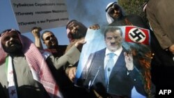Newly elected Kuwaiti deputy Walid Tabtabai (left) holds a burning portrait of Russian President Dmitry Medvedev during a protest in front of the Russian Embassy in Kuwait City on February 6.