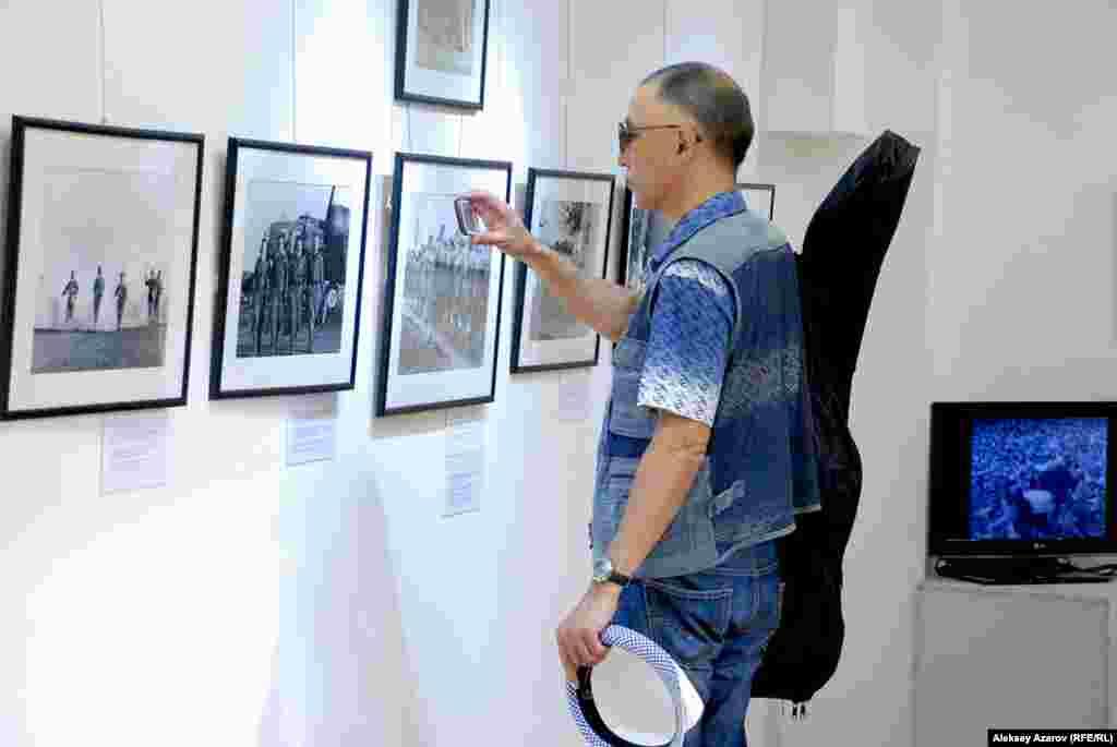 Посетитель выставки «Одна победа», организованной посольством США, фотографирует увиденное на смартфоны.