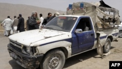 Police examine a damaged police van following a bomb attack in Quetta.