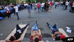 Armenia -- Demonstrators lie on Marshal Bagramian Avenue during a protest against an increase of electricity prices in Yerevan, June 24, 2015