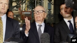 "Media mogul Rupert Murdoch (center) talks to reporters after a July 15 meeting with the family of a murdered schoolgirl, Milly Dowler, whose phone had been hacked for ""News of the World"" reporting."