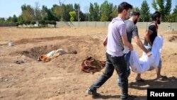 Люди ховають тіло однієї з жертв імовірної хімічної атаки в околицях Дамаска