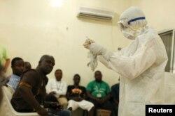 Либерияда жергілікті дәрігерлерге Эбола вирусына қарсы сақтық шараларын үйретіп жатқан маман.