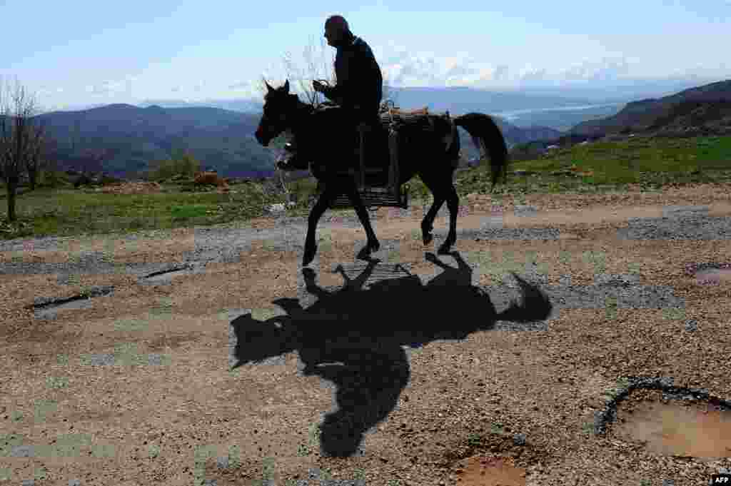 A man rides a horse in the mountains of Tunceli Province.