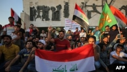 Iraqis holding national flags demonstrate against unemployment in the capital Baghdad's Tahrir Squareon July 14, 2018. Two demonstrators were killed in southern Iraq, officials said, as protests against unemployment spread today from the port city of Basr
