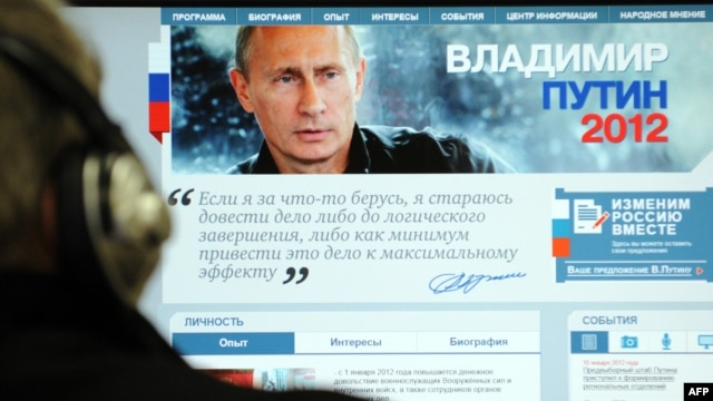 A man looks at a computer monitor displaying the main page of Prime Minister Vladimir Putin's election campaign website.