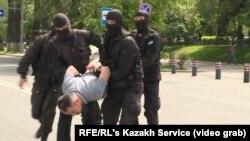 Сотрудники полицейского спецназа несут задержанного на несанкционированной акции протеста. Алматы, 10 мая 2018 года.