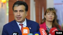 Georgian President Mikheil Saakashvili (left), accompanied by his wife, Sandra Roelofs, speaks to journalist during parliamentary elections at a polling station in Tbilisi on October 1.