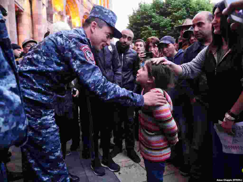"Thousands took to the streets of the Armenian capital, Yerevan, on April 20 for an eighth-straight day to protest the election of former President Serzh Sarkisian as prime minister. Here, 6-year-old Lucine Burtoyan said to a police officer guarding the government building: ""Come with us. Why are you with [Sarkisian]? Why aren't you with your people?"" (RFE/RL/Amos Chapple)"
