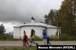 Tajik women collect their children from a kindergarten near a church in Rozhdestveno.