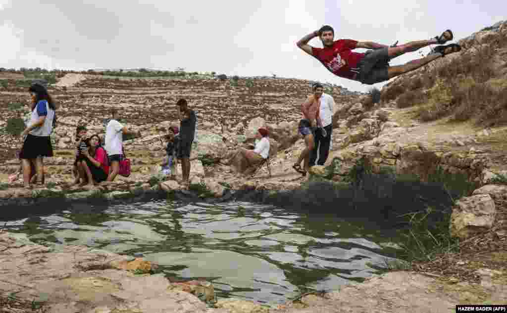 A man poses while jumping into a pool near the Palestinian village of Doura, west of Hebron in the West Bank. (AFP/Hazem Bader)