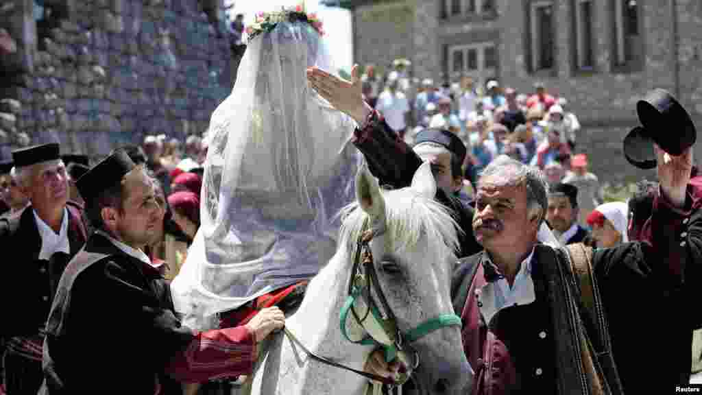 Macedonian bride-to-be Danica Torteska is led on horseback to her husband by her father-in-law and marriage witnesses during a wedding ceremony in the village of Galicnik on July 15. (REUTERS/Ognen Teofilovski)