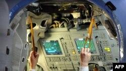 Руки космонавта Федора Юрчихина під час тренувань у наземній копії корабля «Союз», квітень 2013 року
