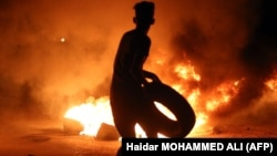 A demonstrator burns tires during protests in the southern Iraqi city of Basra on July 12.