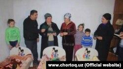 Чиновники Чартакской районной администрации в доме новорожденных тройняшек, названных в честь Зироатхон Мирзияевой и ее дочерей.