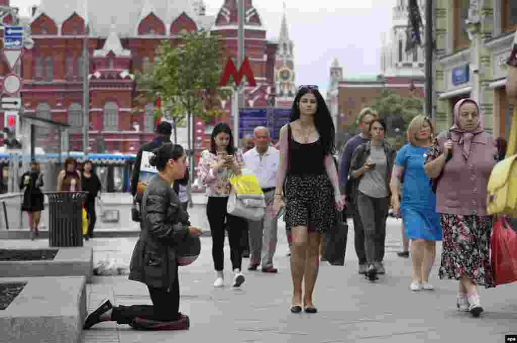 A pregnant woman begs on the newly renovated Tverskaya Street in Moscow. (epa/Yuri Kochetkov)
