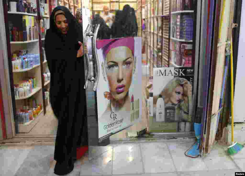 A woman walks out of a cosmetics shop in Sadr City.