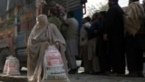 A woman, clad in burqa, carries a sack of flour, purchased from a truck along a road in the northwestern city of Peshawar on January 20.