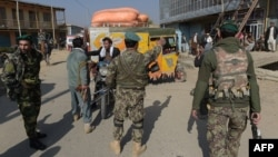 Afghan security personnel stop man a roadblock following an attack on the U.S. military base in Bagram on November 12.