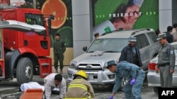 Rescue personnel take away the body of a bomb blast victim near the main gate of a supermarket in Kabul.