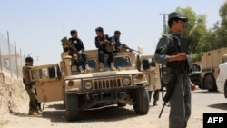 Afghan security personnel sit atop an armored vehicles amid an ongoing battle with Taliban militants in the Gereshk district of Helmand Province on July 22.