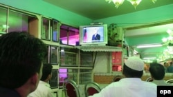 Afghans watch the debate at a shop in Kabul.