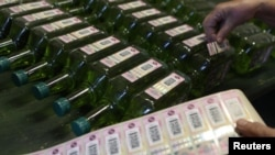 Наклеивание наклеек на бутылки с алкоголем. Чехия, 20 сентября 2012 года.
