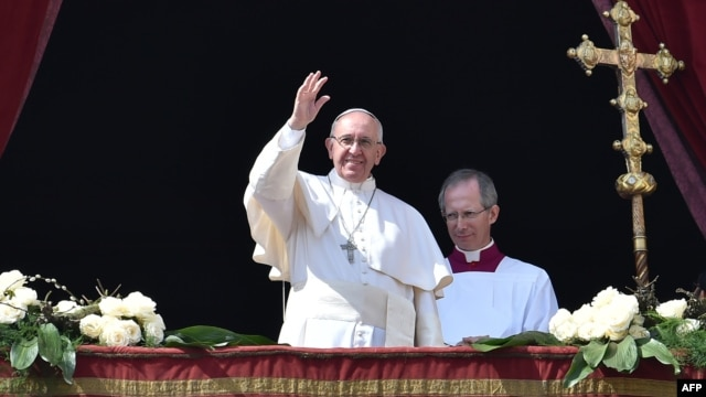 Pope Francis gestures to crowds at St. Peter's Basilica in Rome following Easter Sunday Mass on March 27.