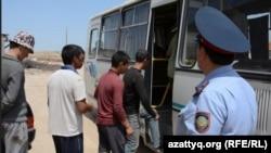 Полицейский наблюдает за посадкой в автобус задержанных в связи с предполагаемым нарушением миграционного законодательства.