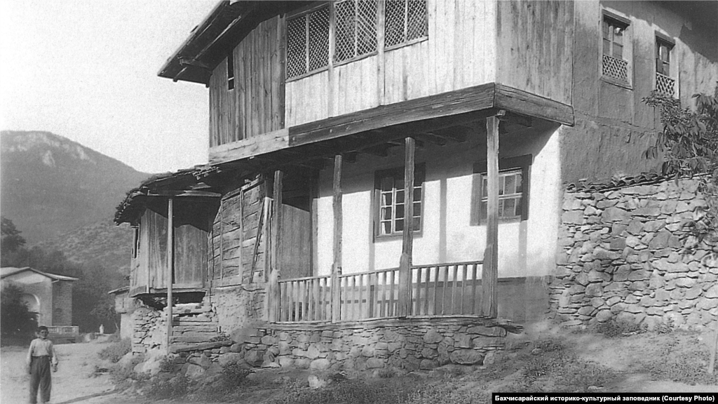 A house in southwestern Crimea, 1920s. The standard interior of the main room included an open fireplace with a chimney and a cauldron suspended from it on a chain. Along the walls, there were low sofas with mattresses and pillows. Numerous towels were used to decorate the walls, and there were carpets on the floor.