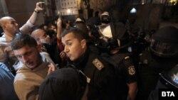 Напрежението между полицаи и протестиращи във вторник в София ескалира, след като група младежи с качулки атакуваха входа на втората сграда на парламента с бомбички, боя, камъни и бутилки със запалителни течности