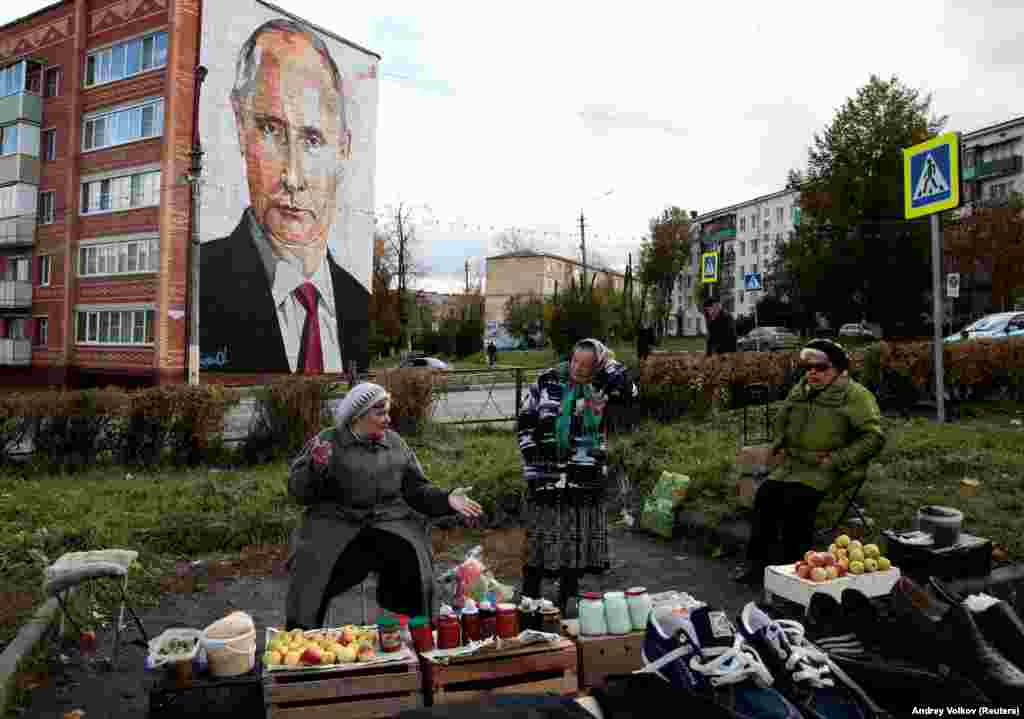 Elderly women in the town of Kashira outside Moscow wait for customers as they sell food products at a street market with a graffito depicting Russian President Vladimir Putin on the wall in the background. (Reuters/Andrey Volkov)