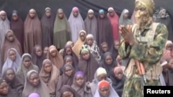 A still image from a video posted by the Nigerian Islamist militant group Boko Haram, showing a masked man talking to dozens of girls who had been kidnapped in the town of Chibok in 2014.