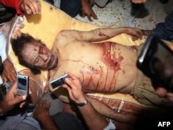 Ливийцы снимают на сотовые телефоны тело убитого Муаммара Каддафи. Мисурата, 20 октября 2011 года.