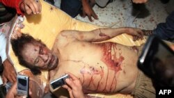 Libya -- Libyans take pictures with their mobile phones of the body of Muammar Qaddafi in Misrata, 20Oct2011 !!GRAPHIC CONTENT