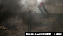 Чоловік тримає палестинський прапор під час сутичок з ізраїльськими військовими на знак протесту проти рішення президента США Дональда Трампа визнати Єрусалим столицею Ізраїлю, неподалік кордону з Ізраїлем в південній частині Смуги Гази, 7 грудня 2017 року