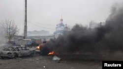 Cars burn on a street in Mariupol after the east Ukrainian city was hit by shelling on January 24.