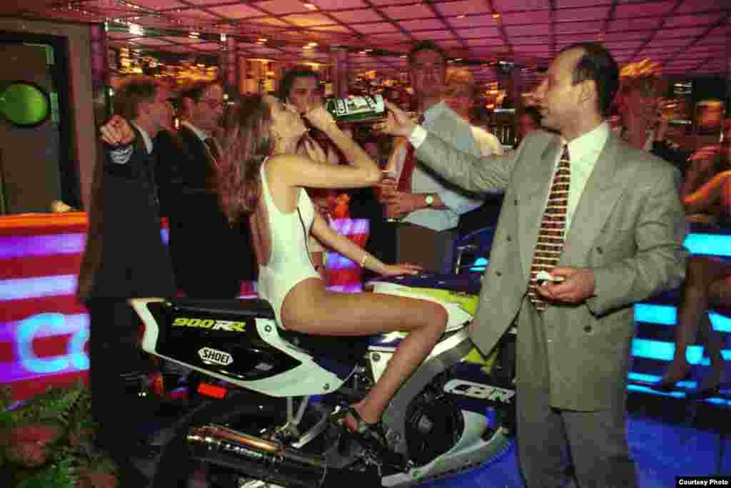 """Посетители клуба """"Up&Down"""" предлагают девушке-модели восстановить силы глотком алкоголя в перерыве между показами нижнего белья, 1996."""