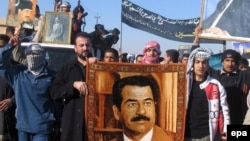 Iraqis in Tikrit protest carry portraits of Saddam Hussein at a demonstration in 2007, the year after his execution.