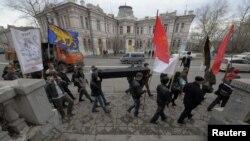 Участники акции протеста несут символический черный гроб и флаги. Владивосток, 6 мая 2012 года.