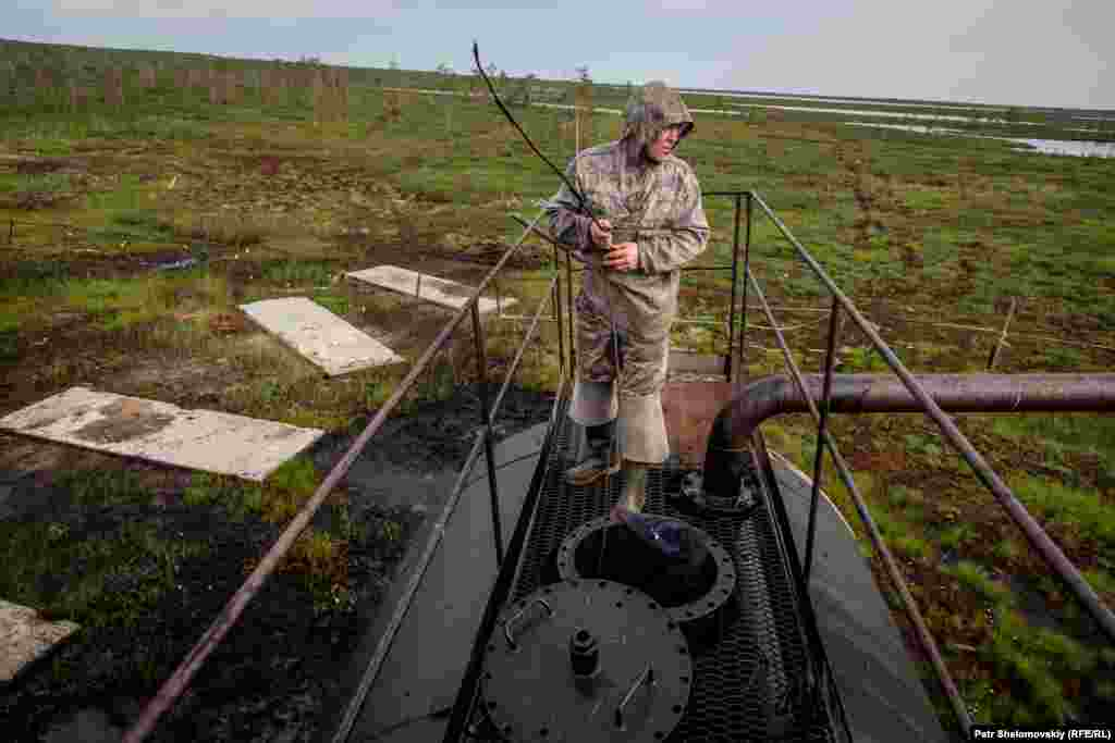Sergey Multanov measures the oil level in an abandoned well used for exploratory drilling.